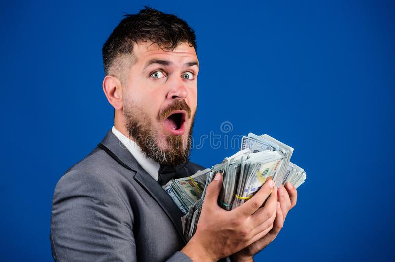 Cash transaction business. Man happy winner rich hold pile of dollar banknotes blue background. Easy cash loans stock image