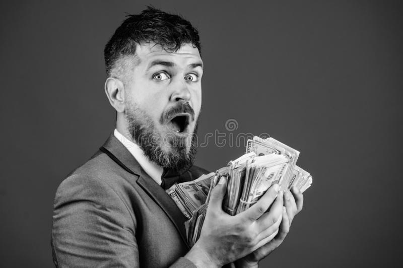 Cash transaction business. Man happy winner rich hold pile of dollar banknotes blue background. Easy cash loans stock photography
