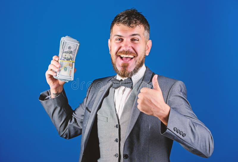 Cash transaction business. Man happy winner rich hold pile of dollar banknotes blue background. Easy cash loans. Win stock images