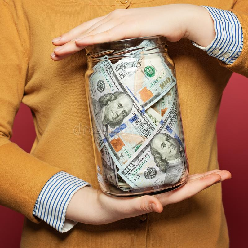 Cash us dollars in jar on colorful bright background. Saving money concept stock photos