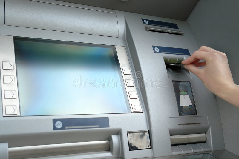 Cash withdrawal. Closeup of woman's hand inserting e-card into ATM slot stock images