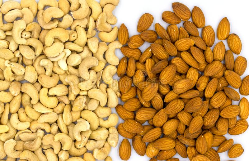 Cashew and almond nut heap on white background, top view photo. Scattered nut on table. Organic food stock image
