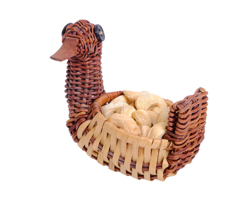 Cashew nuts in a wicker bowl in the form of a duck royalty free stock photography
