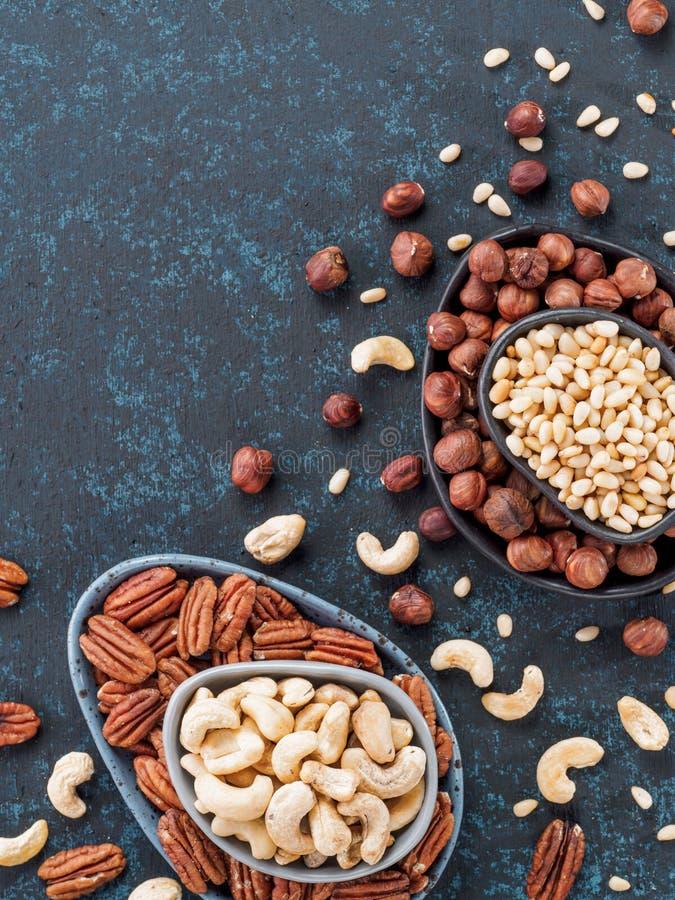 Cashew, pecan, pine nuts, hazelnuts on blue stock image