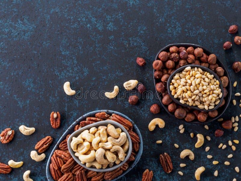 Cashew, pecan, pine nuts, hazelnuts on blue stock photo