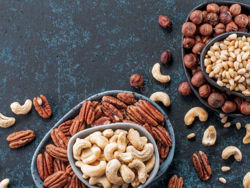 Cashew, pecan, pine nuts, hazelnuts on blue royalty free stock photo