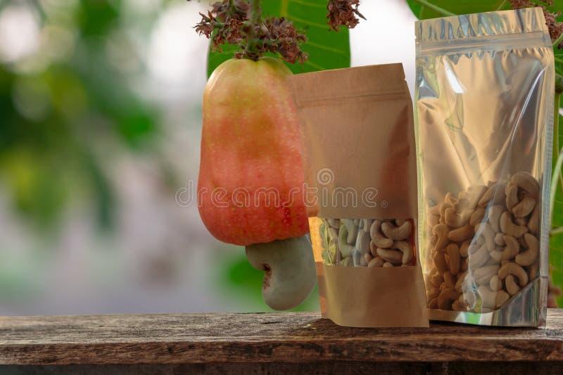 Cashewnoten in de verpakkende zak met rood rijp fruit royalty-vrije stock foto