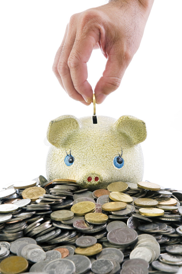 Hand putting coin into piggybank royalty free stock image