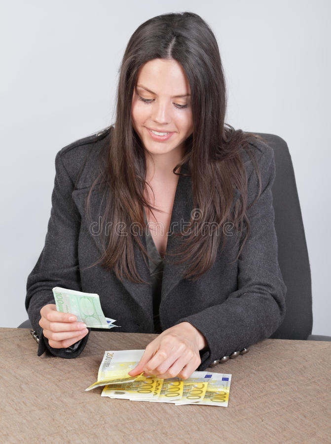 Cashier counting euros. Attractive smiling young businesswoman, cashier or accountant sitting on a table counting cash money, euro banknotes, as if paying out royalty free stock photo