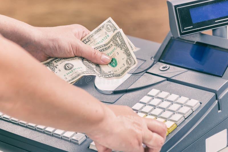 Cashier holdnig banknotes. And using cash register at shop stock images