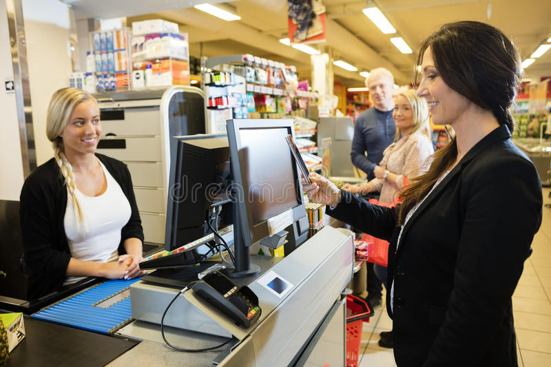Cashier Looking At Female Customer Making NFC Payment. Smiling cashier looking at female customer making NFC payment at checkout counter in grocery store stock image