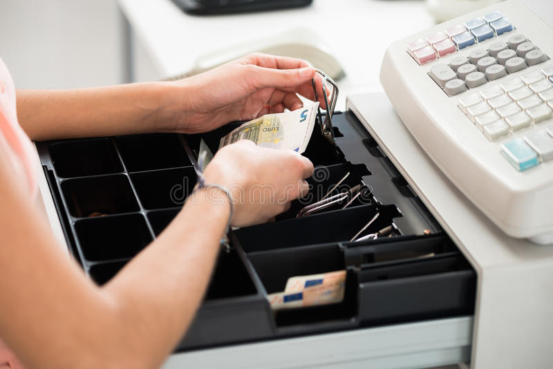 Cashier Searching For Change In Cash Register Drawer. High angle view of female cashier searching for change in cash register drawer at supermarket stock images