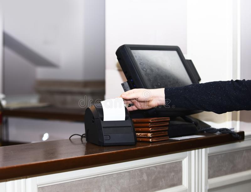 Cashier takes bill out of bill machine in restaurant. Cashier takes bill out of bill machine near sensor screen in restaurant. Cash counter and cashier machine stock images