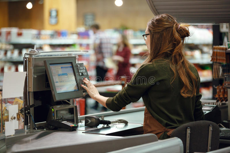 Cashier woman on workspace in supermarket shop. Back view photo of cashier women on workspace in supermarket shop. Looking aside royalty free stock photos