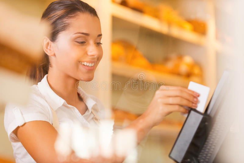 Cashier at work. Attractive young female cashier swipes a plastic card through a machine and smiling royalty free stock photography