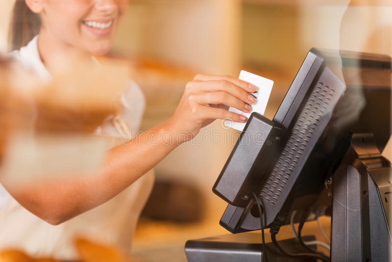 Cashier at work. Beautiful young female cashier swipes a plastic card through a machine stock photography