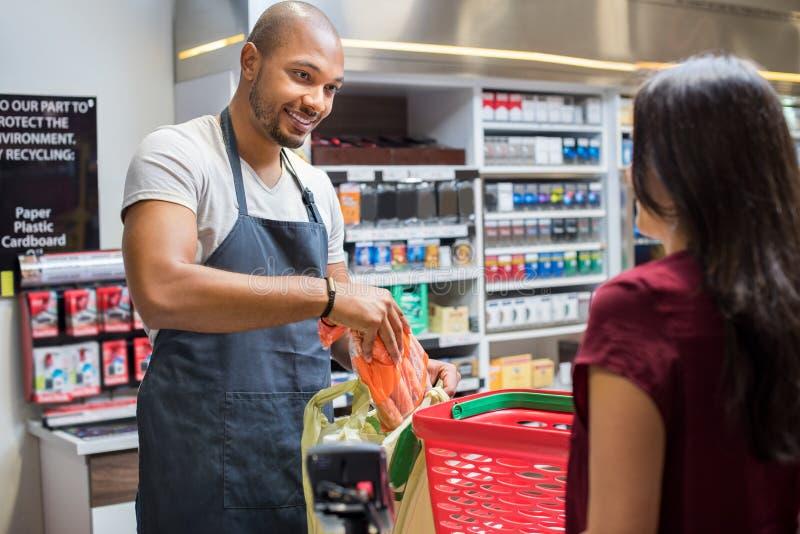 Cashier working at supermarket. Smiling salesman putting vegetables in bag for customer after billing. Cashier black men at grocery store helping customer pack royalty free stock photo