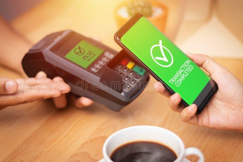 Cashless samhälle, kund som betalar räkningen till och med smartphonen genom att använda NFC-teknologi på punkt av försäljningste royaltyfri foto