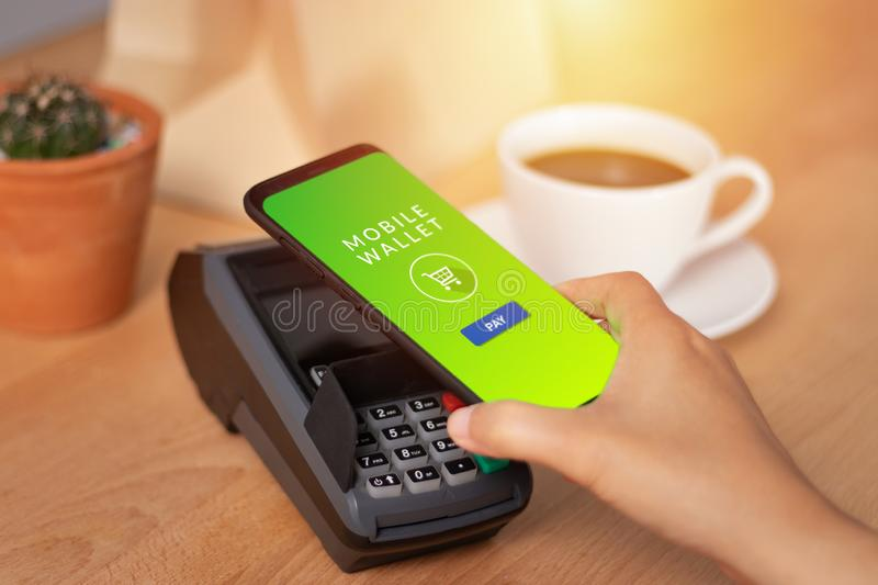 Cashless Society, customer paying bill through smartphone using NFC technology in cafe. mobile digital wallet technology concept. royalty free stock image