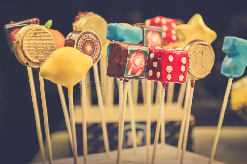 Casino cake pops. Different shapes of casino themed cake pops on the sticks on black background. Gambling, game, entertainment, hedonism and consumerism stock photography