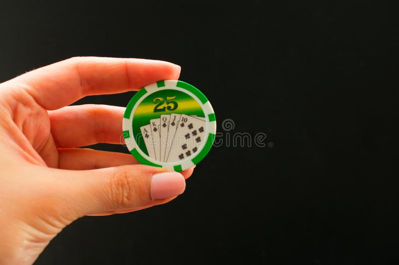 Casino chips in female hand on a black background. stock image