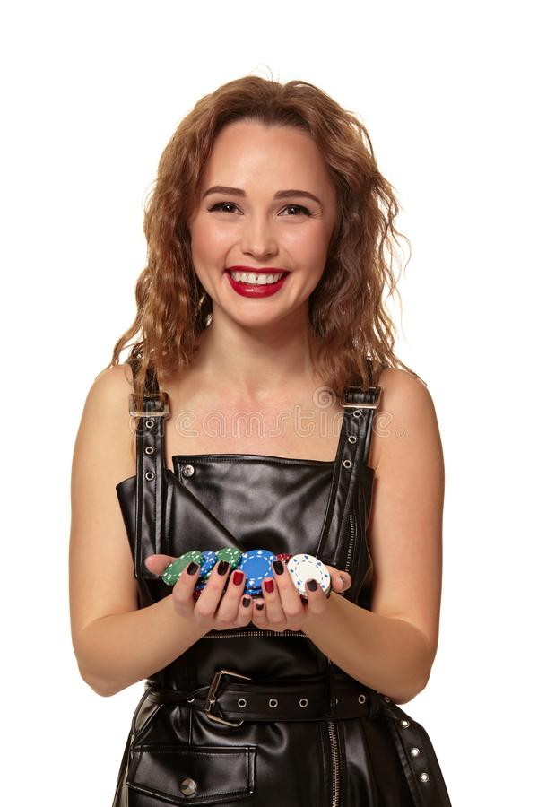 Casino concept. Portrait of young pretty caucasian woman, playing in casino. Roulette, poker chips, cards, wheel. Attractive young caucasian redhead woman in stock image