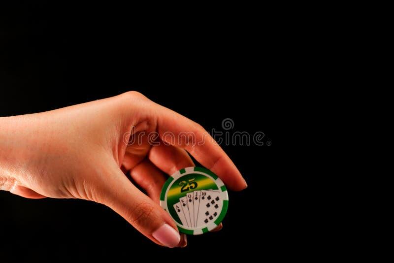 Casino da microplaqueta na mão fêmea em um fundo preto imagem de stock
