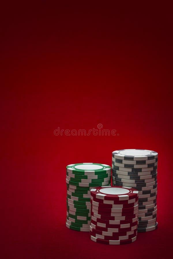 Casino en het gokken concept met drie stapels spaanders van verschillend kleuren rood, groen en wit die grijs op een gevoeld rood royalty-vrije stock afbeeldingen