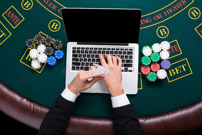 Casino, en línea juego, tecnología y concepto de la gente - cercano para arriba de jugador de póker con los naipes fotos de archivo libres de regalías