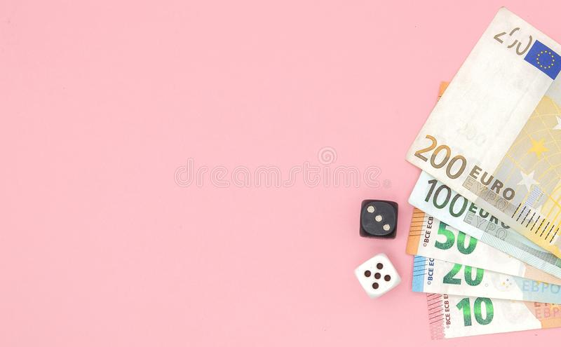 Casino, gambling and fortune concept - close up of black and white dice and euro money on pink background with copy space royalty free stock images