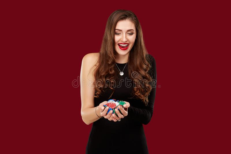 Casino, gambling, poker, people and entertainment concept - woman poker player in black dress with chips in hands on red. Background. Studio shot royalty free stock photos