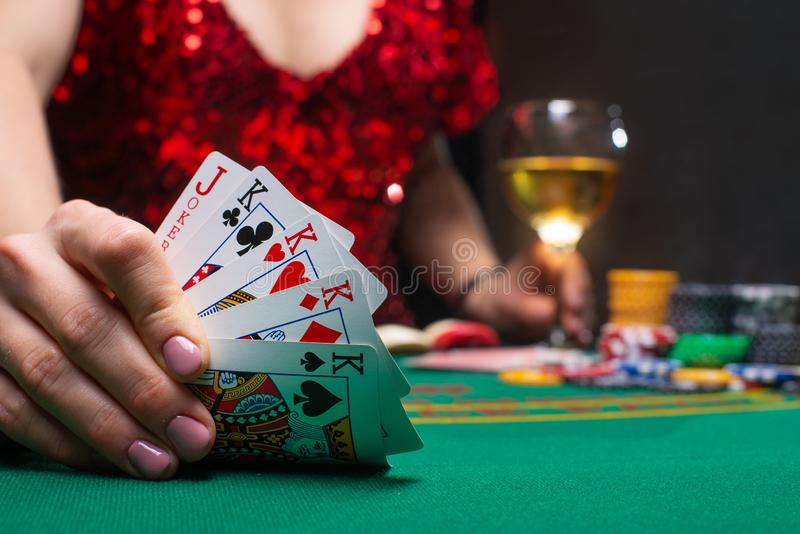 Casino games. A girl in a red evening dress and plays poker in a night casino. covers cards, gaming business.  royalty free stock photos