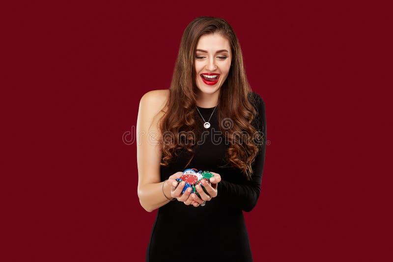 Casino, het gokken, pook, mensen en vermaakconcept - de speler van de vrouwenpook in zwarte kleding met spaanders in handen op ro royalty-vrije stock foto's