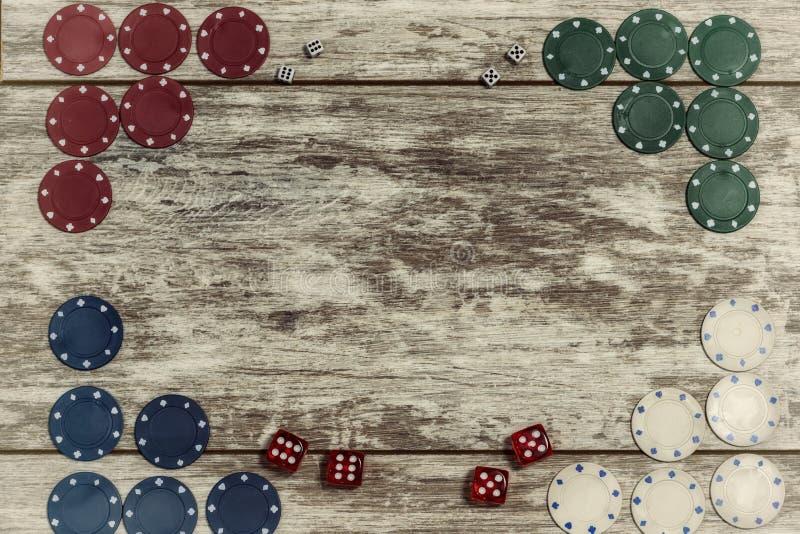 Casino het spelen de spaanders en dobbelen op een lichte houten achtergrond worden opgemaakt op de randen met de capaciteit om ee stock foto's