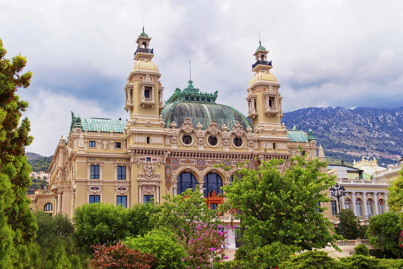 Casino Monte Carlo behind blooming trees. In front of cloudy sky in summer royalty free stock photography