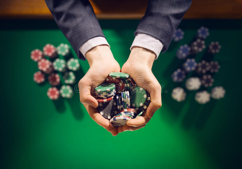 Casino playes holding a handful of chips stock photography