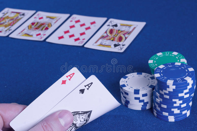 Casino poker hand. Pocket aces poker hand with cards on the board and big stack chips royalty free stock image