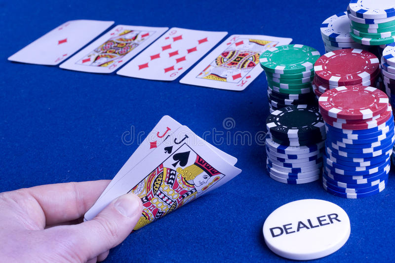 Casino poker hand. Pocket jacks poker hand with cards on the board and big stack chips stock photo