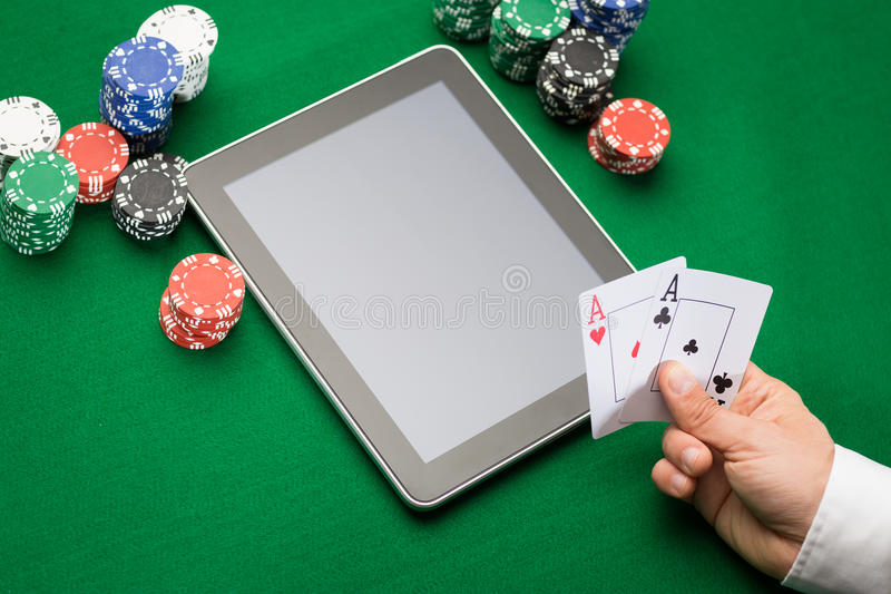 Casino poker player with cards, tablet and chips. Casino, online gambling, technology and people concept - close up of poker player with playing cards, tablet pc royalty free stock images