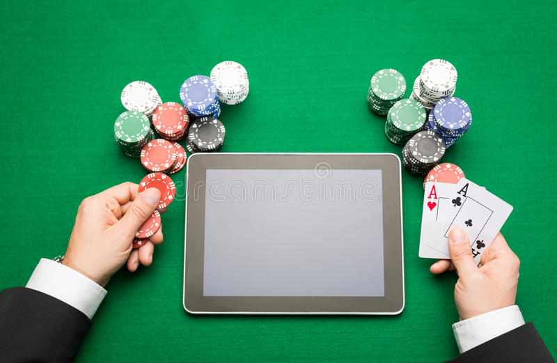 Casino poker player with cards, tablet and chips. Casino, online gambling, technology and people concept - close up of poker player with playing cards, tablet pc stock images