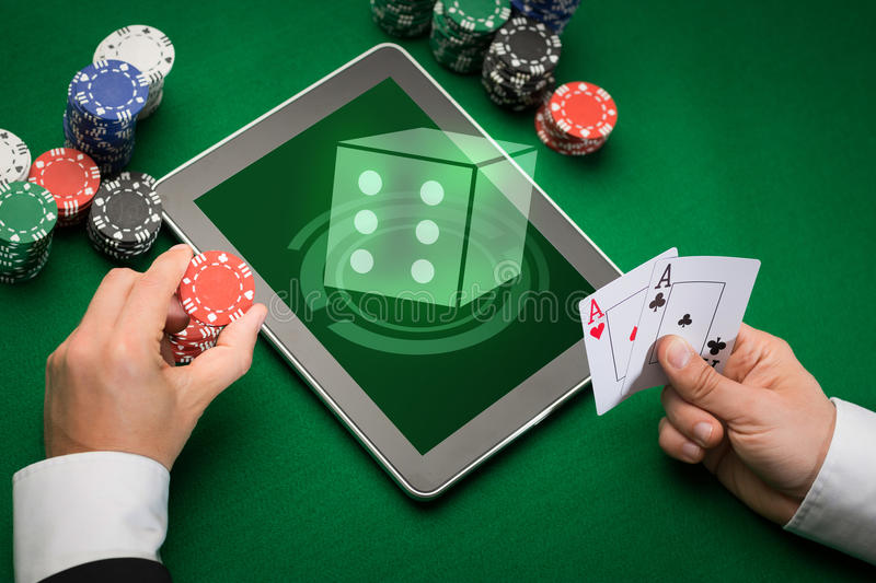 Casino poker player with cards, tablet and chips. Casino, online gambling, technology and people concept - close up of poker player with playing cards, tablet pc stock image