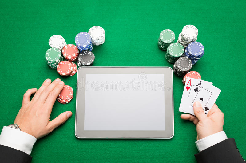 Casino poker player with cards, tablet and chips. Casino, online gambling, technology and people concept - close up of poker player with playing cards, tablet pc royalty free stock image
