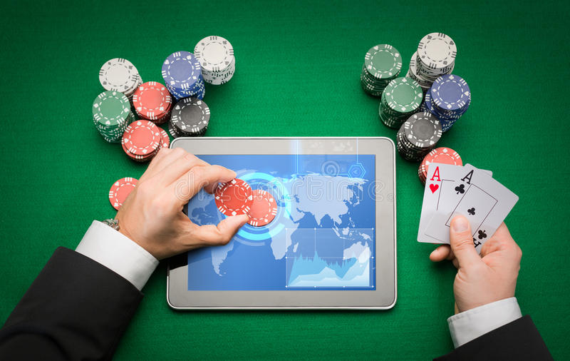 Casino poker player with cards, tablet and chips. Online casino, worldwide gambling, technology and people concept - close up of poker player with playing cards royalty free stock photo