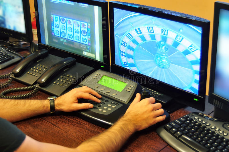 Casino surveillance. Real casino surveillance operator watching roulette on monitor stock photo
