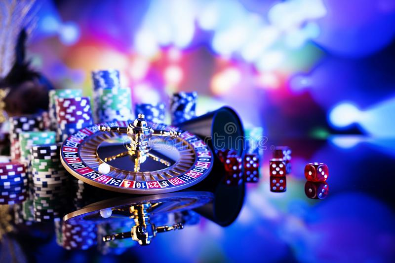 Casino theme background.  Gambling games. Roulette, dice and poker chips on a colorful bokeh background stock photo