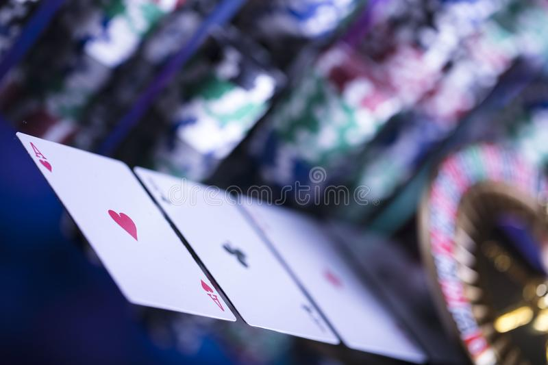 Casino theme. High contrast image of casino roulette, poker game, dice game, poker chips on a gaming table, all on colorful bokeh background royalty free stock photography