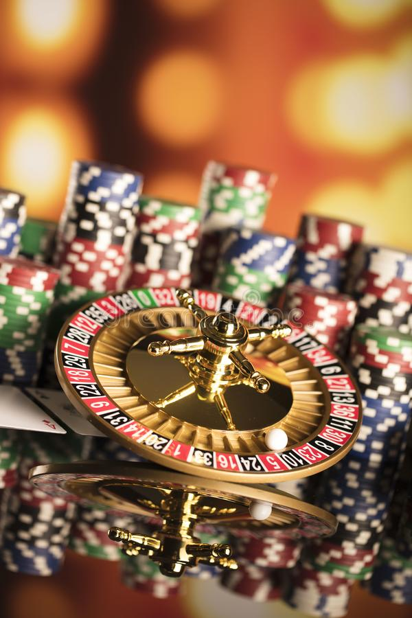Casino theme. High contrast image of casino roulette, poker game, dice game, poker chips on a gaming table, all on colorful bokeh background stock photography