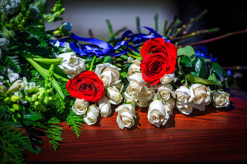 Casket Flowers. Flowers on casket, Red and white roses with a blue ribbon stock image