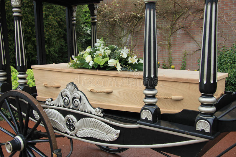 Casket on a funeral carriage. Wooden casket with funeral flowerson a funeral carriage royalty free stock image
