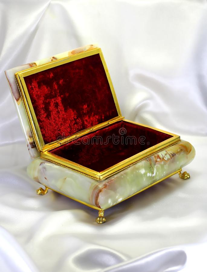 Casket from onyx in a gold frame. On a white silk background stock photos